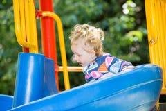 Menina adorável feliz na corrediça das crianças no campo de jogos perto do jardim de infância Montessori Fotos de Stock Royalty Free