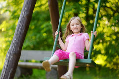 Menina adorável que tem o divertimento em um balanço Fotografia de Stock Royalty Free