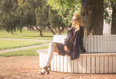 Menina adulta nova que senta fora a luz solar Fotografia de Stock