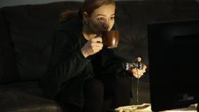 Menina adulta que joga jogos de computador mulher que senta-se no sofá e que guarda o console do jogo Apego de jogo vídeos de arquivo