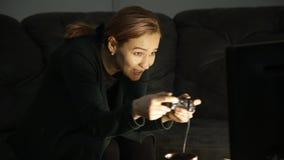 Menina adulta que joga jogos de computador mulher que senta-se no sofá e que guarda o console do jogo Apego de jogo video estoque