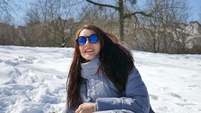 Menina adulta surpreendente em óculos de sol espelhados azuis e nas bolas de neve de jogo retas do cabelo escuro que jogam com al vídeos de arquivo
