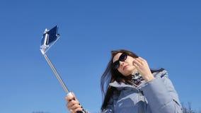 Menina adulta surpreendente nos óculos de sol escuros que levantam ao tomar um selfie fora no parque usando seus smartphone e var video estoque