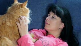 A menina afaga um gato vermelho filme