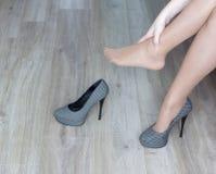 A menina aferra-se à canela, sapatas, saltos, fadiga na fadiga dos pés foto de stock