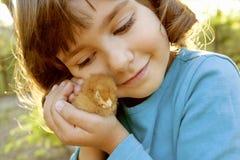 A menina afetuosa que guarda a galinha nas mãos gosta de um tesouro Fotos de Stock Royalty Free