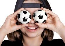 A menina afortunada no boné de beisebol fechado seus olhos com as bolas de futebol Imagens de Stock Royalty Free