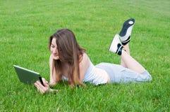 Menina afortunada que encontra-se na grama com tabuleta. imagem de stock royalty free