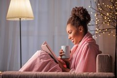 Menina africana alegre que aprecia a literatura e a bebida quente fotos de stock royalty free
