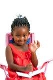 Menina africana bonito com mão de ondulação do livro de nota. fotografia de stock