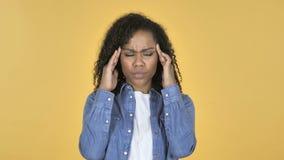 Menina africana com dor de cabeça isolada no fundo amarelo filme
