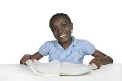 Menina africana com livro de texto Fotografia de Stock Royalty Free