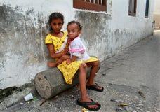 Menina africana de pele escura 8 anos velha, posses uma irmã bienal. Imagem de Stock