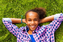 A menina africana de sorriso com em verão coloca na grama Imagens de Stock Royalty Free