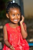 Menina africana feliz que fala no telefone esperto. fotografia de stock royalty free