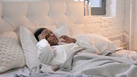Menina africana nova com a dor de cabeça que coloca na cama video estoque