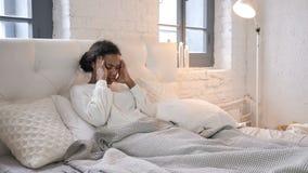 Menina africana nova com a dor de cabeça que relaxa na cama filme