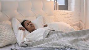 Menina africana nova perturbada que tenta dormir na cama, desassossego filme