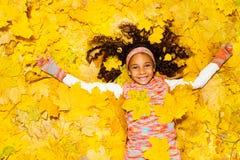 Menina africana pequena sob as folhas de bordo amarelas Fotos de Stock