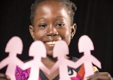 Menina africana que joga com bonecas de papel fotografia de stock