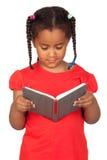 Menina africana que lê um livro foto de stock