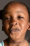 Menina africana que pressiona sua cara contra uma janela imagens de stock