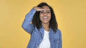 Menina africana que procura a possibilidade nova, fundo amarelo video estoque