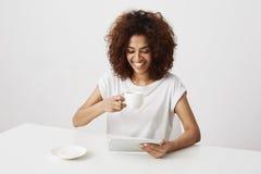 Menina africana que sorri mantendo o copo e a tabuleta que sentam-se na tabela sobre o fundo branco Foto de Stock