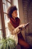 Menina afro-americana com o ipad que está a janela próxima no escritório Fotografia de Stock Royalty Free
