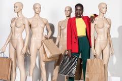 menina afro-americano à moda que sorri na câmera ao estar entre manequins com compra imagem de stock royalty free