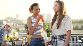 A menina afro-americano bonita está falando a seus amigo caucasiano e cocktail bebendo que guardam a garrafa durante ao ar livre filme