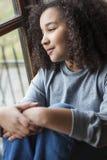 Menina afro-americano da raça misturada que olha fora da janela Imagens de Stock