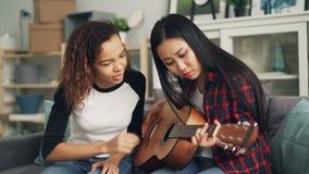 A menina afro-americano de sorriso está ensinando seu amigo asiático jogar a guitarra acústica que fala então dando seu musical vídeos de arquivo