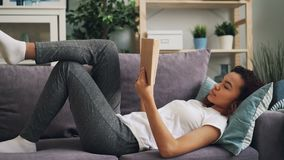 A menina afro-americano esperta é concentrada na novela da leitura do livro que encontra-se no sofá em casa que aprecia a ativida video estoque