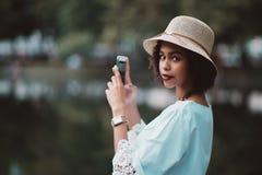 A menina afro-americano está fotografando a água do lago da noite através de imagem de stock