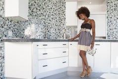 Menina afro-americano nova na cozinha fornecida nova que escolhe materiais Foto de Stock