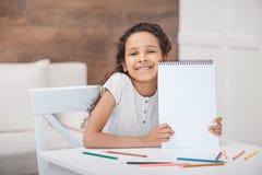 Menina afro-americano que mostra o álbum vazio do desenho Imagem de Stock