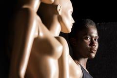 menina afro-americano que olha a câmera ao estar perto dos manequins imagens de stock royalty free