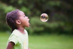 Menina afro-americano que persegue uma única bolha Fotografia de Stock Royalty Free