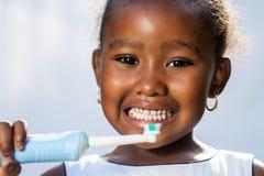 Menina afro pequena bonito que guarda a escova de dentes elétrica imagens de stock