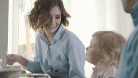 Menina agradável de três anos com seus pais em um café São comem vídeos de arquivo