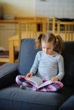 A menina agradável de uma idade escolar mais nova lê o livro fotografia de stock royalty free