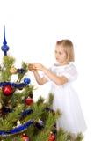 A menina agradável decora uma árvore de Natal Imagem de Stock