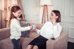 Menina agradável deleitada que dá um copo do chá a sua mãe foto de stock royalty free