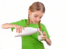 A menina agradável derrama o leite de uma garrafa no vidro imagem de stock royalty free