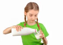 A menina agradável derrama o leite de uma garrafa no vidro fotografia de stock royalty free