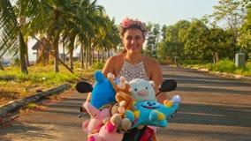 Menina agradável do close up em Garland Rides Moped com brinquedos filme