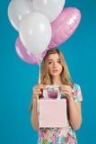 A menina agradável doce com baloons e os prersents pequenos ensacam nas mãos no fundo azul Modo da mola Fotos de Stock