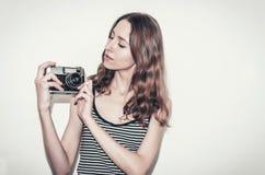 Menina agradável em um t-shirt listrado com uma câmera do vintage em suas mãos Fotografando povos imagem de stock royalty free