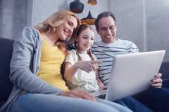 Menina agradável feliz que aponta na tela do portátil imagem de stock